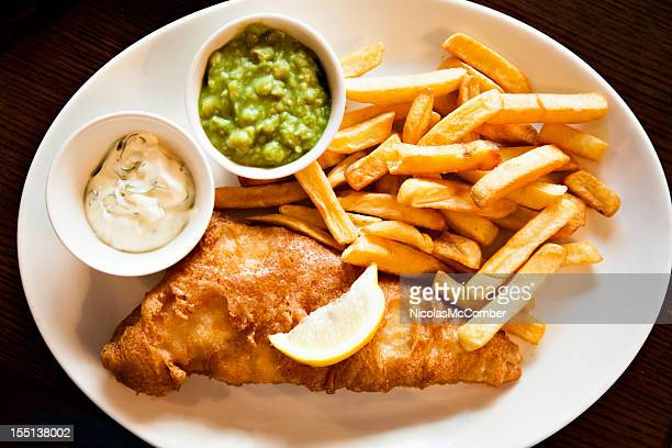 Plate of Fisn and Chips with tartar sauce mushy peas