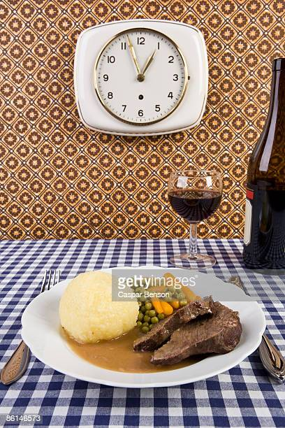 A plate of food with a glass and bottle of wine