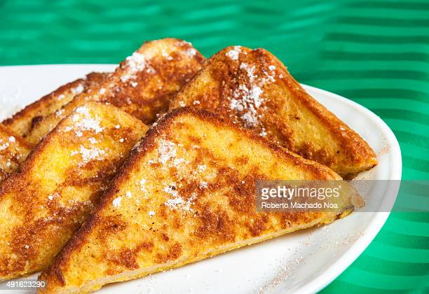 Plate of French toast Five slices of French toast sit on a white plate dusted in powdered sugar The plate is set on top of a green tablecloth