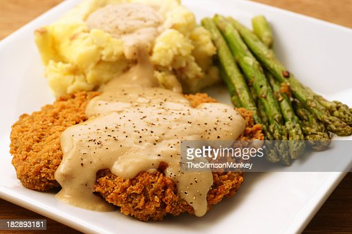 A plate of fried chicken, mashed potatoes and asparagus