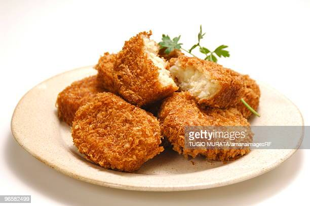 Plate of fried croquettes, close up, white background