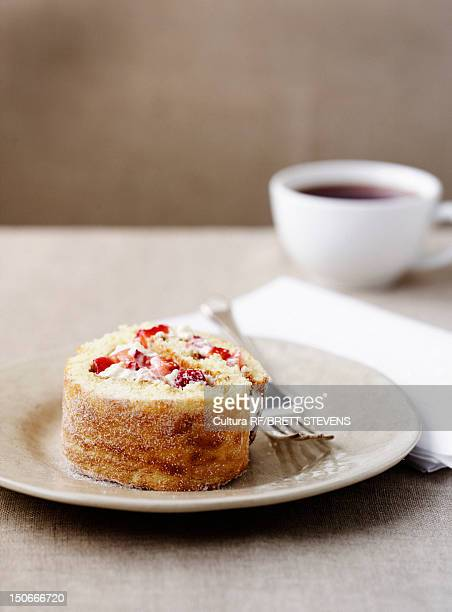 Plate of fruit swiss roll with coffee