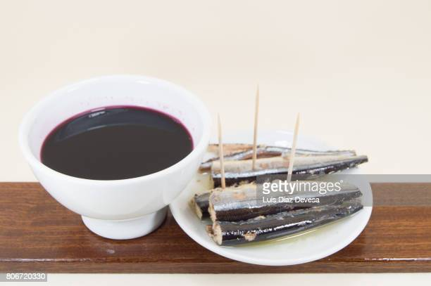 plate of garfish in olive oil and an white earthenware cup of red wine