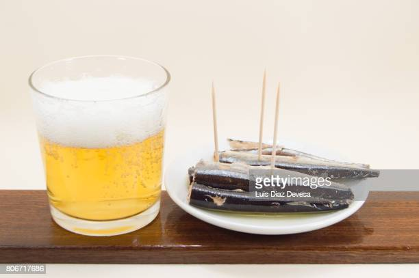 plate of garfish in olive oil and glass of beer