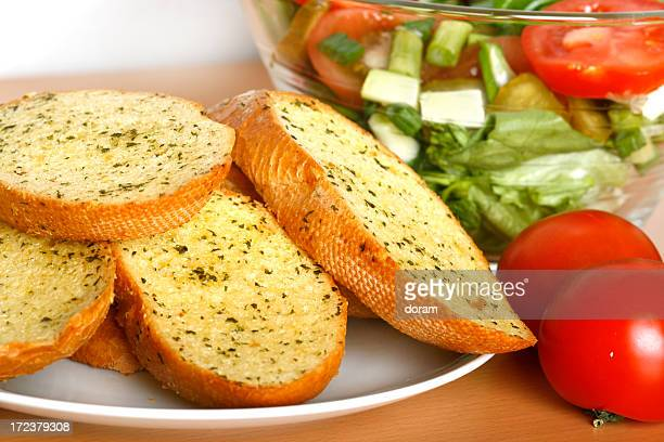 A plate of garlic bread with tomatoes and salad on a table