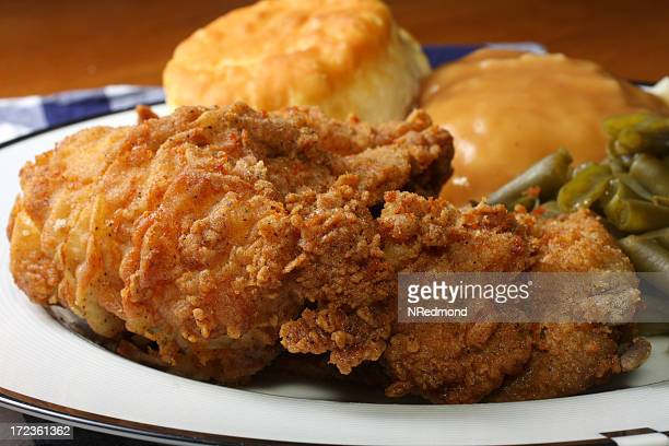 Plate of golden fried chicken with vegetables and a biscuit