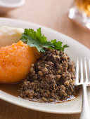 Plate of Haggis Neeps and Tatties On White Plate With Silver Fork