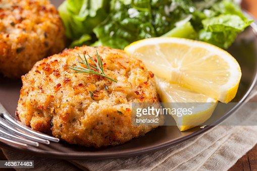 Plate of homemade organic crab cakes with veg and lemon : Stock Photo