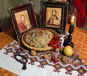 Plate of kutia (sweet grain pudding), traditional Orthodox Easter holiday food, popular in Eastern Europe, in front of icons and lit candle with walnuts, apple, kalina and prayer beads on the table