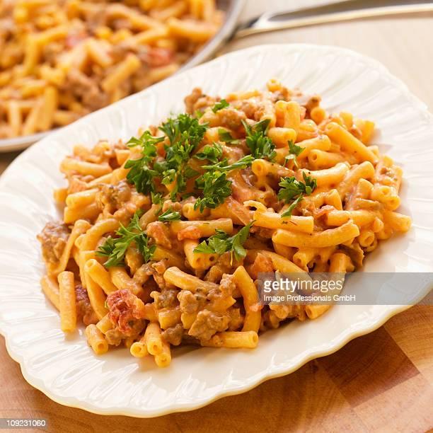 Plate of macaroni dish with salsa and sausage