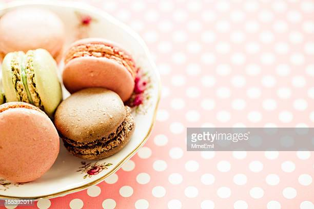 A plate of macaroons on a pink and white dot tablecloth