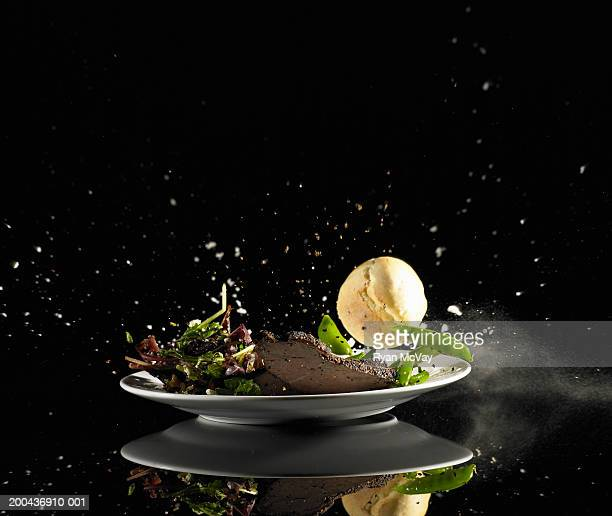 Plate of meat, salad, peas and roll falling to floor