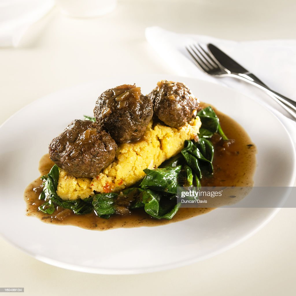 plate of meatballs on cous cous and bed of spinach : Stock Photo