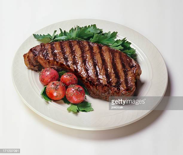 Plate of New York strip steaks with tomatoes on side