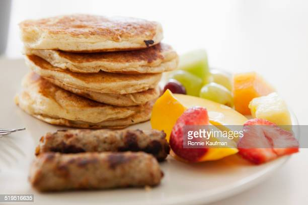 Plate of pancakes, sausage and fruit