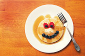 a plate of pancakes and syrup making a funny face with fruit.