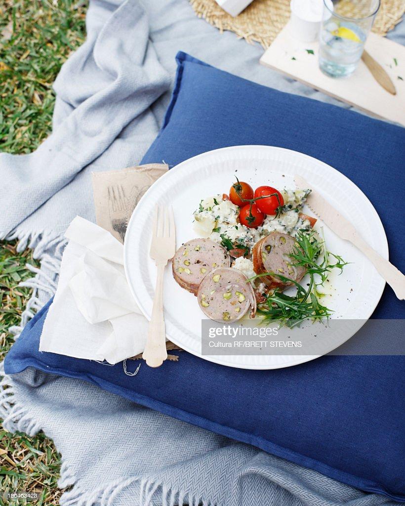 Plate of pork galantine with potato salad and rocket