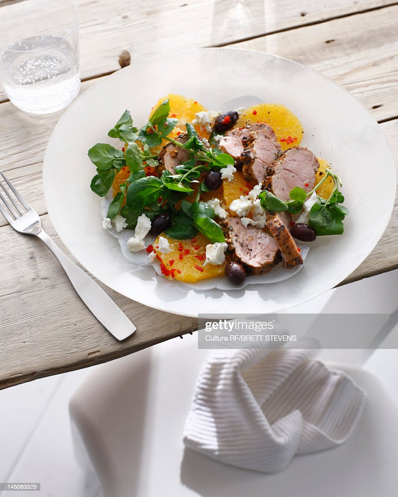Plate of pork with pickled orange salad : Stock Photo