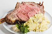 """A white plate of rare prime rib with bone, mashed potatoes and horseradish."""