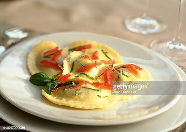 Plate of ravioli with tomatoes and basil, close-up
