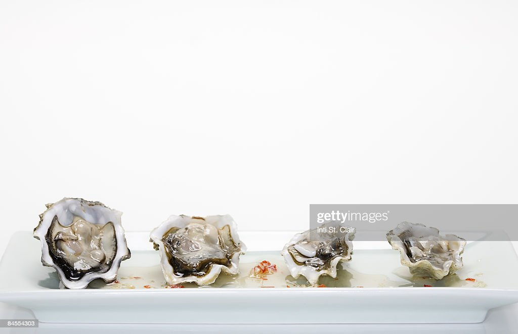 Plate of raw oysters with sweet chili sauce : Stock Photo
