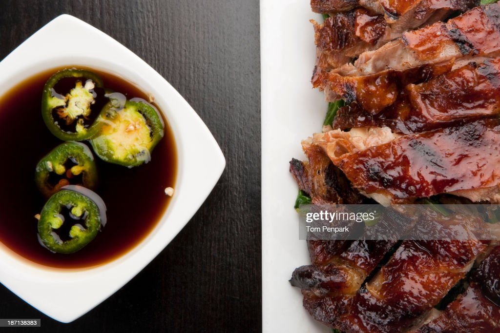 Plate of roasted duck with bowl of jalapenos and soy sauce : Stock Photo