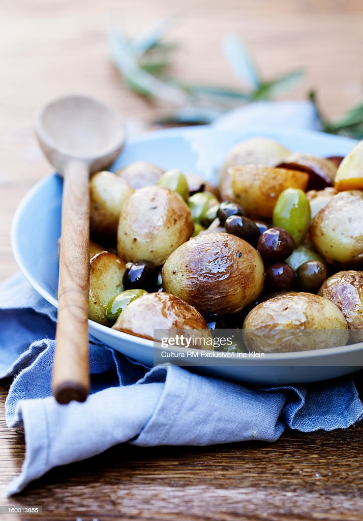 Plate of roasted potatoes and olives : Stock Photo