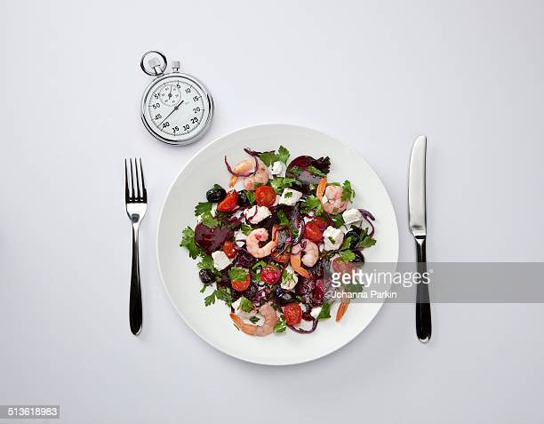 Plate of salad with a stopwatch beside it