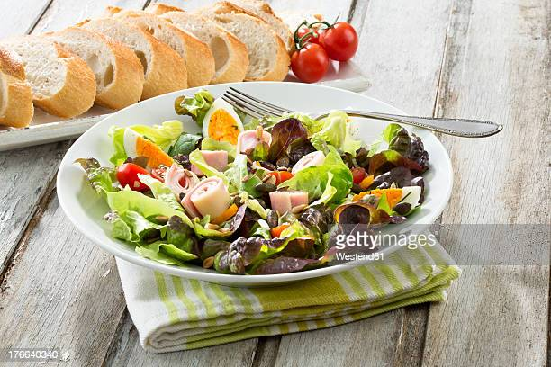 Plate of salad with ham and cheese and bread in tray on table, close up