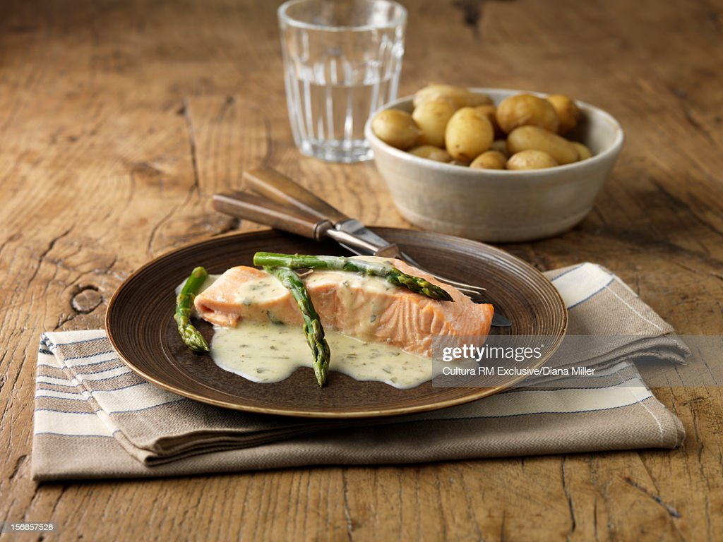 Plate of salmon with asparagus and sauce : Stock Photo