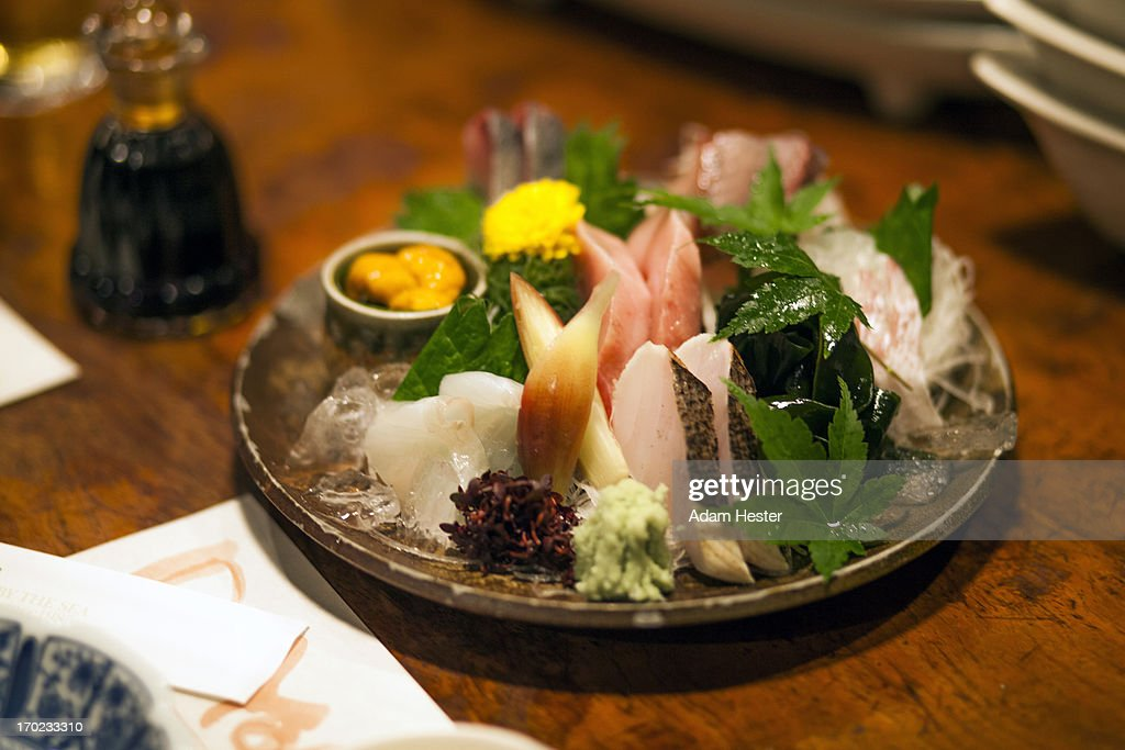 A plate of sashimi and sushi in a restaurant.