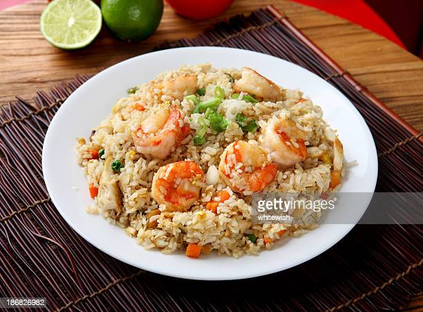 Plate of shrimp fried rice on a placemat and wood table