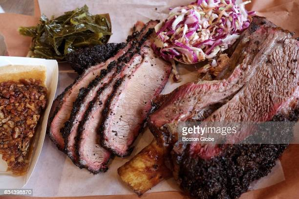 A plate of sliced brisket beef rib collard greens coleslaw and pecan pie is pictured at Killen's Barbecue on Broadway Street in Pearland TX on Feb 4...