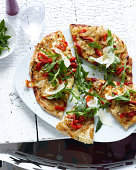 Plate of sliced wholemeal pizza with herbs, vegetable and parmesan