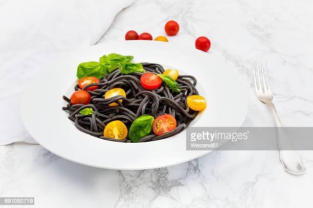 Plate of Spaghetti al Nero di Seppia with tomatoes and basil leaves