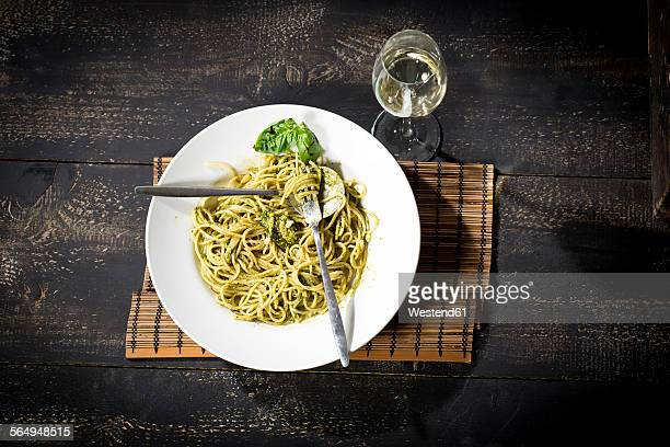 Plate of spaghetti with pesto Genovese and glass of white wine