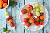 Plate of delicious summer fruit skewers with melon, cheese and prosciutto on a rustic blue wood background