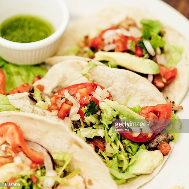 A plate of three tacos with a side of green salsa