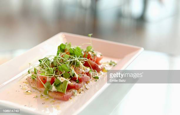 A plate of tuna sashimi with pea shoots on a table