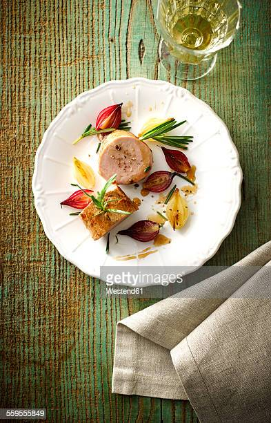 Plate of veal slices, candied and caramelized shallots and a glass of white wine