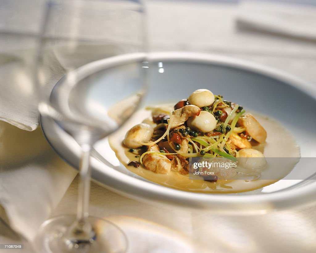 Plate of vegetable with scallops and wine glass : Stock Photo