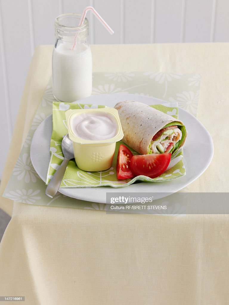 Plate of wrap, yogurt and tomatoes : Stock Photo