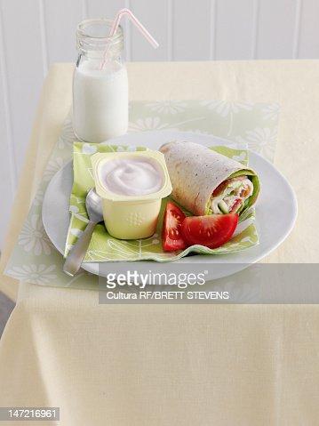 Plate of wrap, yogurt and tomatoes : Stock Photo