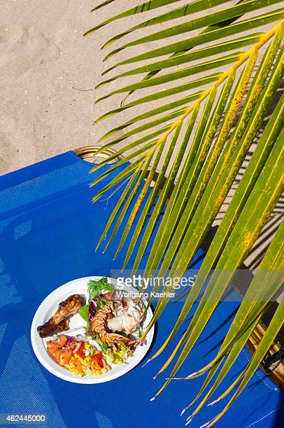 A plate with barbequed lobster chicken and salads on the beach of Mayreau Island a small island in the Grenadines in the Caribbean