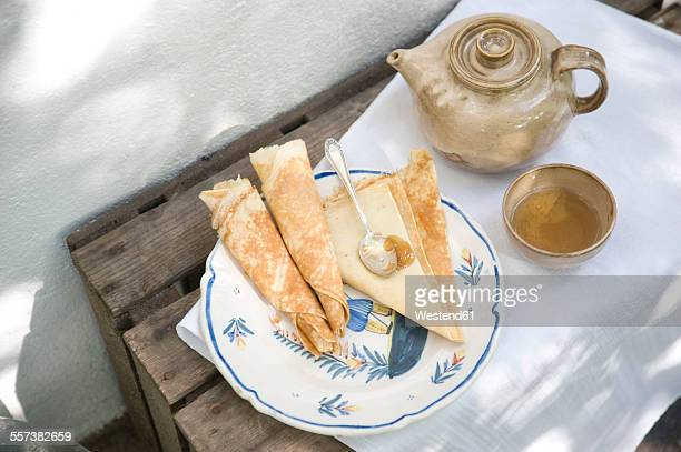Plate with crepes, cup of tea and teapot