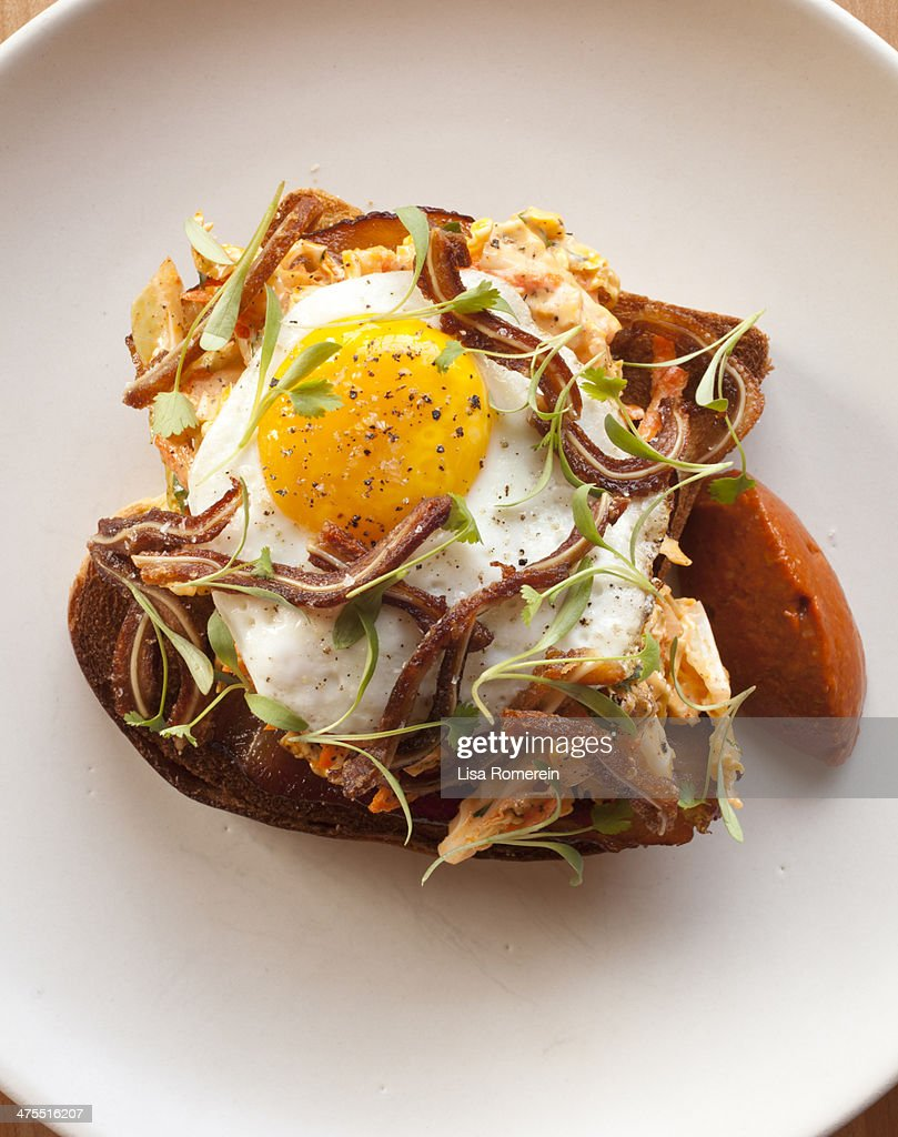 Plate with crispy pig's ear, fried egg and bacon : Stock Photo