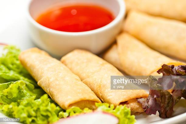 Plate with five fried eggrolls, lettuce and a bowl of sauce