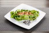 Plate with fresh salmon salad on wicker tablecloth in restaurant