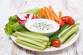 plate with fresh vegetables and thick yoghurt sauce, horizontal