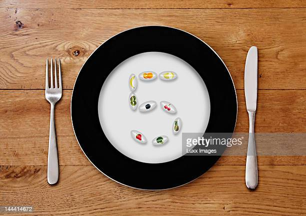 Plate with fruit pills forming a 5